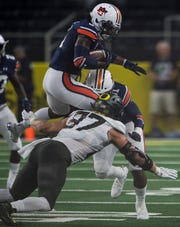 Auburn defensive back Christian Tutt (6) is tackled in the air by Oregon defensive back Max Wysocki (37) on a punt return at AT&T Stadium in Arlington, Texas, on Saturday, Aug. 31, 2019. Auburn defeated Oregon 27-21.