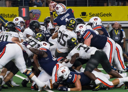 Auburn quarterback Joey Gatewood (1) jumps over his blockers for a touchdown at AT&T Stadium in Arlington, Texas, on Saturday, Aug. 31, 2019. Auburn defeated Oregon 27-21.