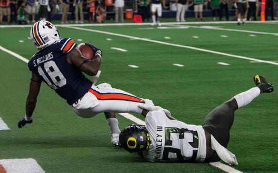 Auburn wide receiver Seth Williams (18) catches the game winning touchdown pass guarded by Oregon defensive back Verone McKinley III (23) at AT&T Stadium in Arlington, Texas, on Saturday, Aug. 31, 2019. Auburn defeated Oregon 27-21.