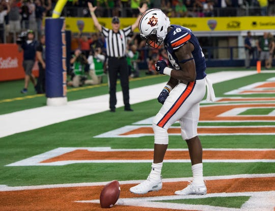Auburn wide receiver Seth Williams (18) spikes the ball in celebration after catching the game winning touchdown pass at AT&T Stadium in Arlington, Texas, on Saturday, Aug. 31, 2019. Auburn defeated Oregon 27-21.