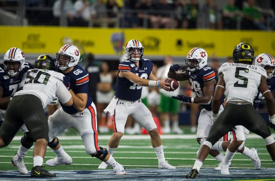 Auburn quarterback Bo Nix (10) hands the ball off to Auburn running back JaTarvious Whitlow (28) at AT&T Stadium in Arlington, Texas, on Saturday, Aug. 31, 2019. Auburn defeated Oregon 27-21.