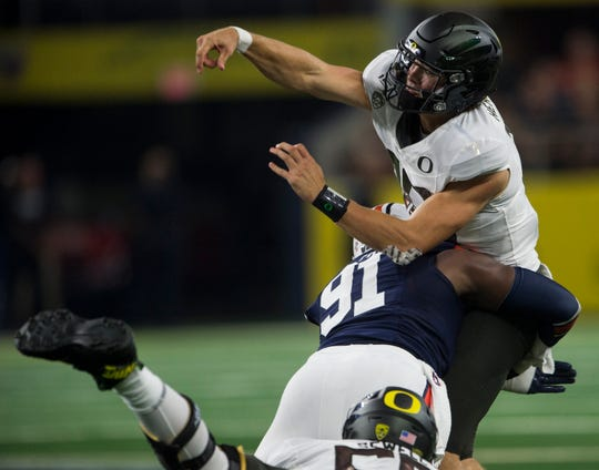 Auburn defensive lineman Nick Coe (91) hits Oregon quarterback Justin Herbert (10) as he throws the ball at AT&T Stadium in Arlington, Texas, on Saturday, Aug. 31, 2019. Auburn defeated Oregon 27-21.