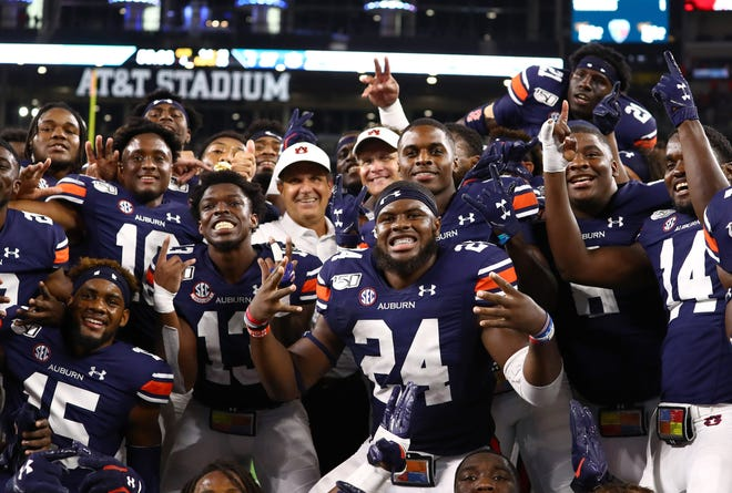 Auburn head coach Gus Malzahn (center right) and defensive coordinator Kevin Steele (center left) celebrate with the team after a victory over Oregon at AT&T Stadium on Aug. 31, 2019.