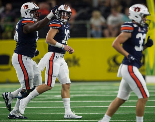 Auburn offensive lineman Prince Tega Wanogho (76) gives a tap to Auburn quarterback Bo Nix (10) after his second interception at AT&T Stadium in Arlington, Texas, on Saturday, Aug. 31, 2019. Auburn defeated Oregon 27-21.