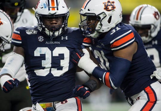 Auburn linebacker K.J. Britt (33) and Auburn linebacker Chandler Wooten (31) react to a big stop at AT&T Stadium in Arlington, Texas, on Saturday, Aug. 31, 2019. Auburn defeated Oregon 27-21.