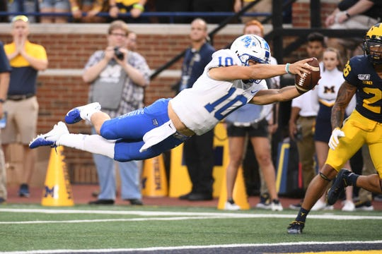 Middle Tennessee Blue Raiders quarterback Asher O'Hara (10) dives to score a touchdown during the first quarter against the Michigan Wolverines at Michigan Stadium.