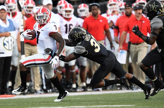 Georgia running back D'Andre Swift (7) moves the ball defended by Vanderbilt defensive back Cam Watkins (31)  during the first half at Vanderbilt Stadium in Nashville, Tenn., Saturday, Aug. 31, 2019.