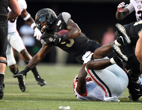 Vanderbilt running back Ke'Shawn Vaughn (5) is tackled by Georgia linebacker Azeez Ojulari (13) during the first half at Vanderbilt Stadium in Nashville, Tenn., Saturday, Aug. 31, 2019.