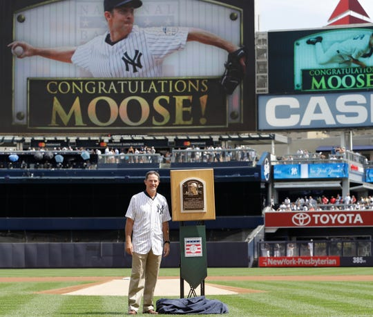 Hall of Fame pitcher Mike Mussina beside his Hall of Fame plaque as he is honored before a baseball game between the Yankees and the Oakland Athletics, Sunday, Sept. 1, 2019, in New York.