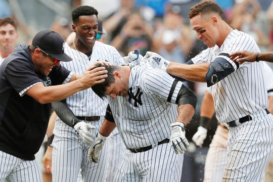 The New York Yankees celebrate with Mike Ford, center, after he hit a walk-off, pinch-hit, solo home run during a baseball game against the Oakland Athletics, Sunday, Sept. 1, 2019, in New York. The Yankees won 5-4.