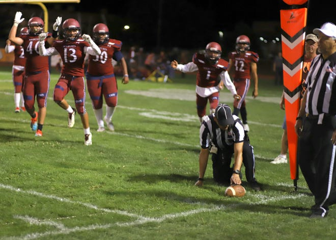 The Deming High defense celebrates after holding the Capital jaguars a yard short on a fourth down measurement at the 8-yard line with a 1:09 left to play to secure a 22-14 Wildcat victory.