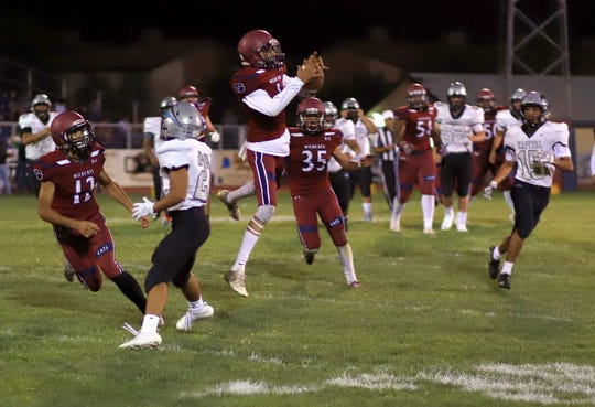 Deming defender Elmer Jabalera (airborne) came away with this interception at the Wildcat 20-yard line to thwart a Capital fourth-quarter scoring threat.
