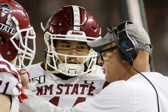 New Mexico State coach Doug Martin, right, speaks with offensive lineman Max Wilhite, left, and quarterback Josh Adkins during the first half of an NCAA college football game against Washington State in Pullman, Wash., Saturday, Aug. 31, 2019. (AP Photo/Young Kwak)
