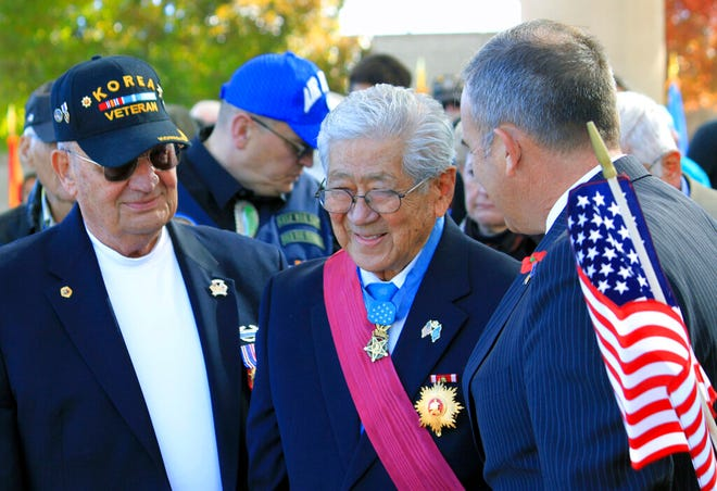 In this Nov. 11, 2014. file photo, people stand to honor Medal of Honor recipient Hiroshi Miyamura, center, during a Veterans Day ceremony at the New Mexico Veterans Memorial in Albuquerque. Miyamura, now 94, the son of Japanese immigrants who was awarded the U.S. Medal of Honor for actions in the Korean War, gave a public lecture last month in Gallup, which an aide said may be his last due to his declining health.