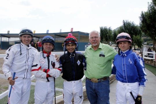 Chaplain Darrell Winter poses with four jockeys before a race at the Ruidoso Downs Racetrack  on Aug. 31, 2019. Winters visits jockeys before races in the jokey room and will even prays with jockeys in the sauna before a race.