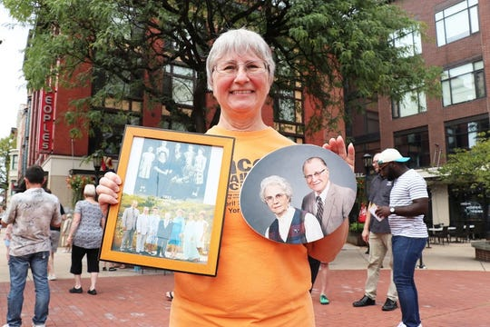 Ann Kemper, of Fireside, brought along her own history to share at the photo recreation event at Continental Square. Kemper posed with photos of her parents and family during the recreation, on Sept. 1, 2019.