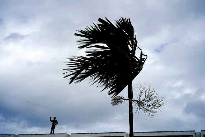 A man stands on a store's roof as he works to prepare it for the arrival of Hurricane Dorian in Freeport on Grand Bahama, Bahamas, Sunday, Sept. 1, 2019. Hurricane Dorian intensified yet again Sunday as it closed in on the northern Bahamas, threatening to batter islands with Category 5-strength winds, pounding waves and torrential rain. (AP Photo/Ramon Espinosa)