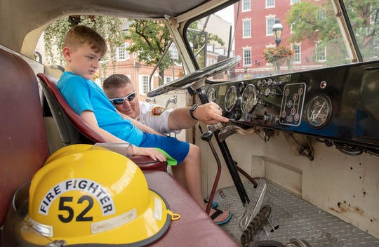 Chad Deardorf, fire chief for the City of York Department of Fire/Rescue Services, right, teaches his son Adam, 9, the manual shift pattern on a 1958 American LaFrance fire engine before a recreation of a 100-year-old photo of a panorama photo of the annual convention and parade of the York County Firemen's Association.