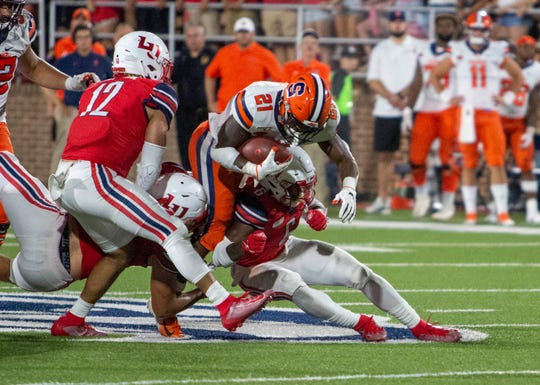 Syracuse running back Moe Neal is stopped by Liberty strong safety Ceneca Espinoza, Jr. during the second half of an NCAA college football game in Lynchburg, Va. Saturday, Aug. 31, 2019. (AP Photo/Matt Bell)/Danville Register & Bee via AP)