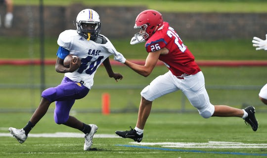 East's Jamaree Gibson, left, is taken down by Fairport's Cameron Bush during a preseason scrimmage at Fairport High School, Saturday, August 31, 2019.