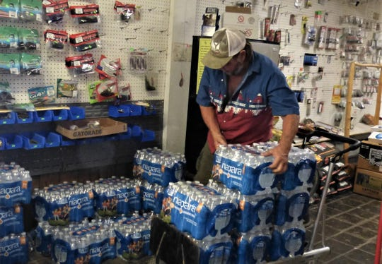 Garry Oliver of Jones Valley unloads cases of water that were donated to Jones Valley residents who have had to boil water before drinking. The water system in the area was affected by the Mountain Fire last month.
