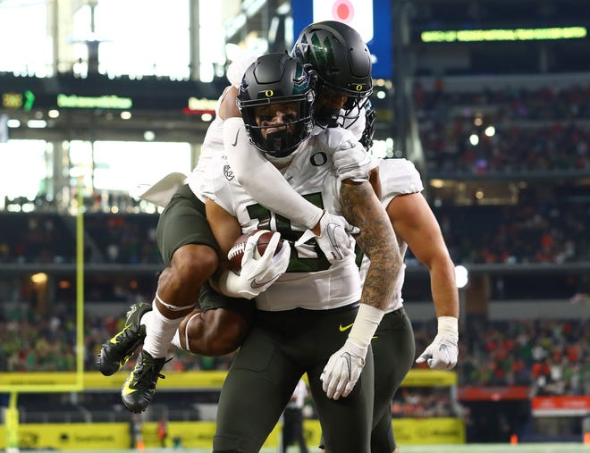 Aug 31, 2019; Arlington, TX, USA; Oregon Ducks tight end Spencer Webb (18) celebrates his first quarter touchdown with receiver Johnny Johnson III (3) on his back against the Auburn Tigers at AT&T Stadium. Mandatory Credit: Matthew Emmons-USA TODAY Sports