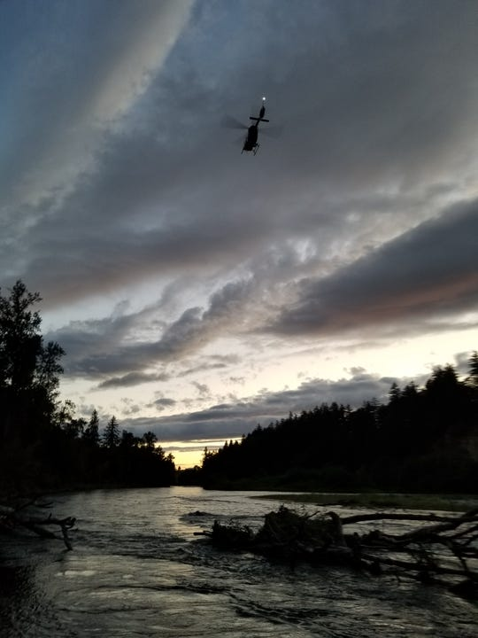 A helicopter flies over the Willamette River near Buena Vista Park in Polk County, Oregon, where a woman was reported missing after hitting a snag while floating the river.