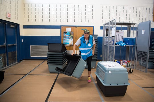 "Martin County employee Kim Tidd helps put crates together at the new pet-friendly shelter at the Willoughby Learning Center in Martin County on Sunday, Sept. 1, 2019, as people in the area prepare for the effects from Hurricane Dorian. Tidd said she will be bringing her family and pets to the shelter later. ""I know for myself and my kids, our dogs are an extension of us, they'e our four-legged fur family,"" she added, touting the emotional benefits of families being able to shelter with their pets. ""I think my daughter is even bringing her fish."""