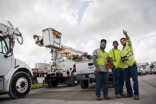 Traveling line workers with New River Electric Corp. Matthew Lacey (left) and Dakota Hollinger watch as coworker Daniel Ownby (right) flies a DJI drone for recreational purposes, while utility crews stage at the St. Lucie County Fairgrounds on Sunday, Sept. 1, 2019, before the effects of Hurricane Dorian are predicted to impact the region as a tropical storm.