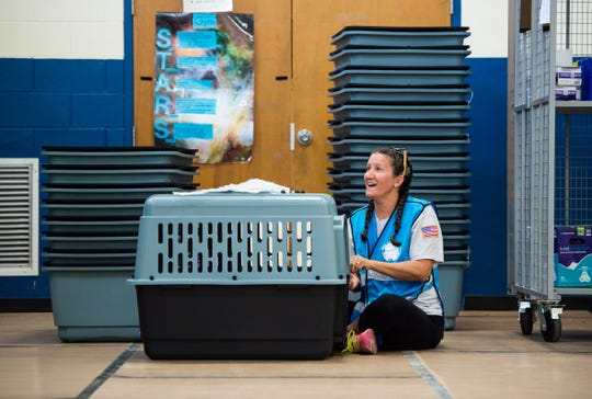 "Martin County employee Kim Tidd helps put crates together at the new pet-friendly shelter at the Willoughby Learning Center in Martin County on Sunday, Sept. 1, 2019, as people in the area prepare for the effects from Hurricane Dorian. Tidd said she will be bringing her family and pets to the shelter later. ""I know for myself and my kids, our dogs are an extension of us, they'e our four-legged fur family,"" she added, touting the emotional benefits of families being able to shelter with their pets. ""I think my daughter is even brining her fish."""