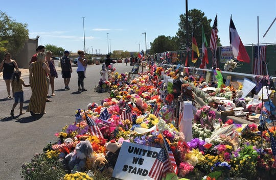 People visit the El Paso Walmart shooting memorial site on Sunday, Sept. 1, 2019.