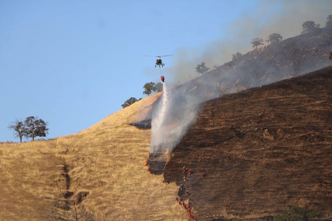 CAL Fire crews work to contain a 680-acre wildfire about 30 minutes east of Woodlake, near Dry Creek Preserve.