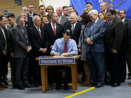Then-Gov. Gov. Scott Walker signs a right-to-work bill into law on March 9, 2015 in Brown Deer, Wisconsin.