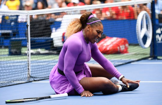 Serena Williams reacts after she rolled her right ankle after a fall at the net.