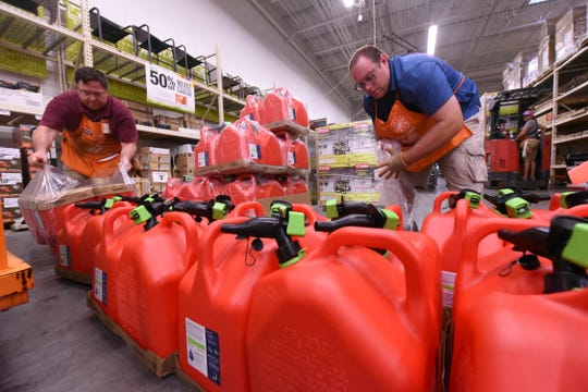 Mark Bratton and Chris Earley put out gas tanks at the Home Depot in Monkey Junction, near Wilmington, on Sept. 2, 2019.