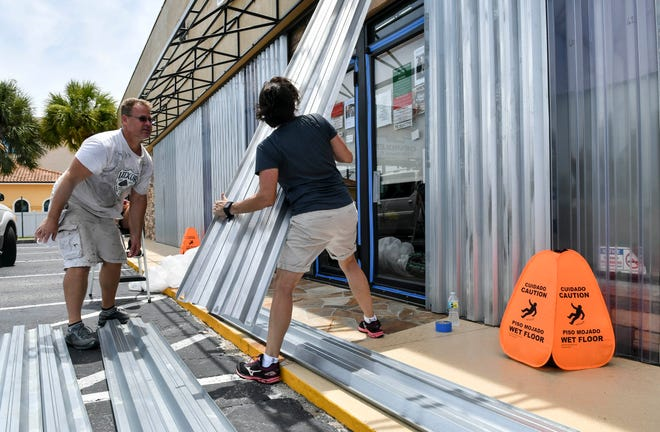 Davin and Sherry Ruohomaki install storm shutters at K9 Campus pet boarding facility in Melbourne, in advance of Hurricane Dorian's arrival on the Space Coast.