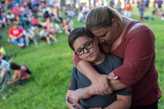 Lorrin Weekes holds her son, 10-year-old Austyn, during a candlelight vigil in Odessa on Sept. 1, 2019. The event was held to remember those who lost their lives in a shooting rampage the day before.
