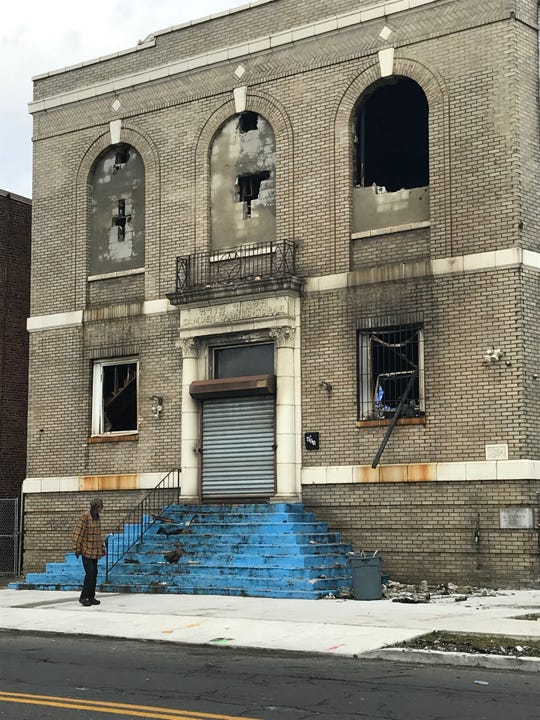 Pedestrian gazes at damage Monday from a blaze that gutted a former synagogue on the 600 block of Kaighn Avenue in Camden one day earlier.
