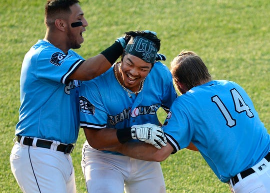 Erie SeaWolves players Isaac Paredes, left, Chace Numata, center, and Cam Gibson, right, celebrate Numata's sacrifice fly to win Game 1 of a doubleheader against the Trenton Thunder on July 25, 2019 at UPMC Park.