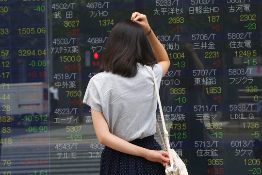 A woman looks at an electronic stock board of a securities firm in Tokyo, Monday, Sept. 2, 2019. Asian stock markets are mixed after Washington and Beijing stepped up their trade war with a new round of tariff hikes.