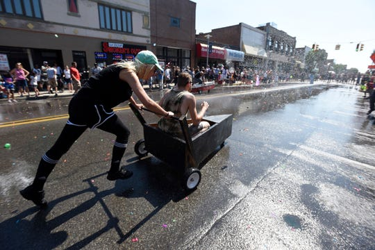 Participants race through the street past residents tossing water balloons in this Sept. 5, 2016 file photo.