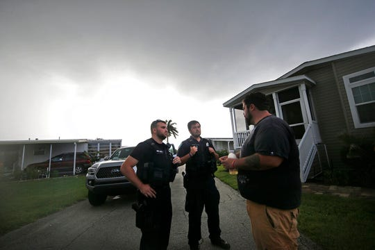 Vero Beach police officers Chayse Hatfield, center, and James Doty talk to resident Todd Dufresne, right, as they notify residents of a trailer park community of a mandatory evacuation, in preparation for Hurricane Dorian, in Vero Beach, Fla., Monday, Sept. 2, 2019. Some coastal areas are under a mandatory evacuation since the path of the storm is still uncertain.