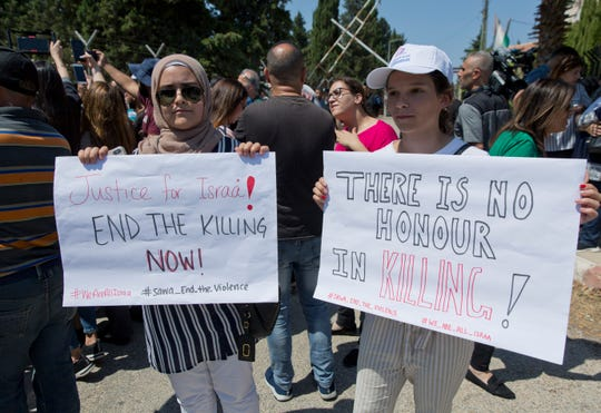 Two Palestinian women hold placards during a rally in front of the Prime Minister's office, in the West Bank city of Ramallah, Monday.