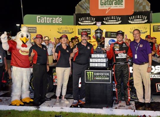 Erik Jones poses with the trophy after winning Sunday's NASCAR Cup Series race Sunday at Darlington Raceway.