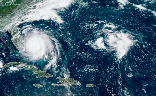 This GOES-16 satellite image taken Monday, Sept. 2, 2019, at 16:40 UTC and provided by National Oceanic and Atmospheric Administration (NOAA), shows Hurricane Dorian, left, churning over Bahamas.