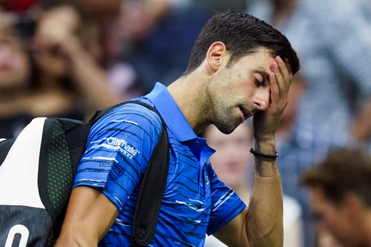 Novak Djokovic walks off the court as he retires during his match against Stan Wawrinka during the fourth round of the U.S. Open tennis championships Sunday in New York.