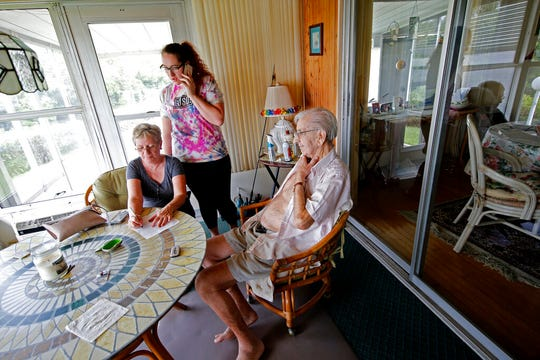 Amalie Hennech, left, and her daughter Alexis Garlini, writes directions to her home, after trying unsuccessfully to evacuate her elderly friend Jack, right, who has advanced medical issues, from the Fairlane Harbor Homes, a trailer park community next to Indian River, during a mandatory evacuation, in preparation for Hurricane Dorian, in Vero Beach, Fla., Monday, Sept. 2, 2019.