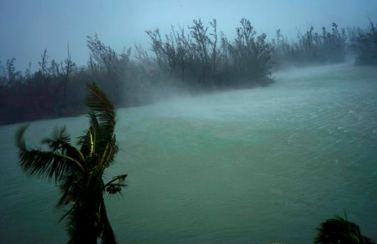 Strong winds from Hurricane Dorian blow the tops of trees and brush while whisking up water from the surface of a canal that leads to the sea, located behind the brush at top, seen from the balcony of a hotel in Freeport, Grand Bahama, Bahamas, Monday, Sept. 2, 2019.