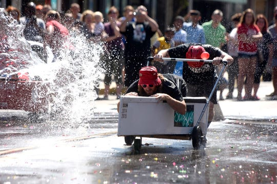 Participants race through the street past residents tossing water balloons in this Sept. 5, 2016, file photo during the Hamtramck Yacht Club Canoe Races , part of the Hamtramck Labor Day Fest in downtown Hamtramck.