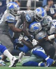 The Lions' Quandre Diggs, Jarrad Davis and A'Shawn Robinson bring down Cowboys running back Ezekiel Elliott in the first quarter of a game last season.